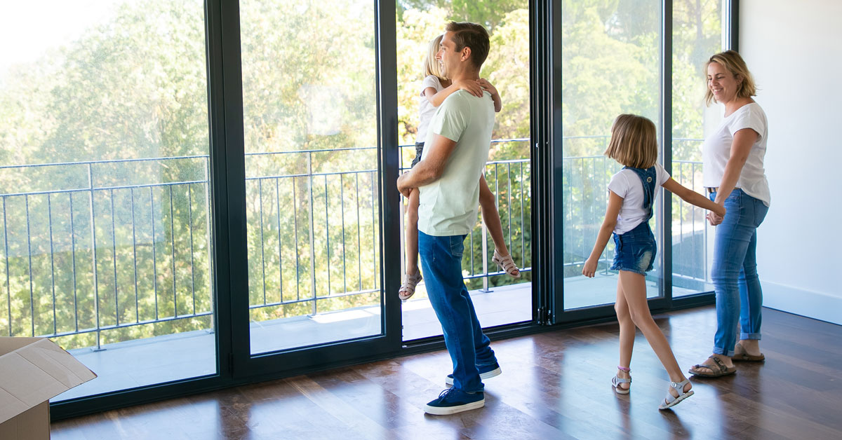 happy-father-with-daughter-standing-near-open-balcony-smiling